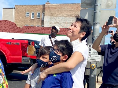 Dr. Lisa Abrams hugs her grandsons Jackson (left) and Carter Abrams as they watch a crew install a street sign honoring Dr. Abrams' parents, Paul and Susie Fong, who founded Chef Shangri-La restaurant 44 years ago at 26th Street and Desplaines Avenue. (Bob Uphues/Editor)