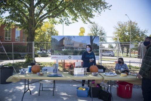 """Employees set up a table and answer questions on Sept. 19, during the """"topping off"""" ceremony at the Brookfield Public Library. (Alex Rogals/Staff Photographer)"""