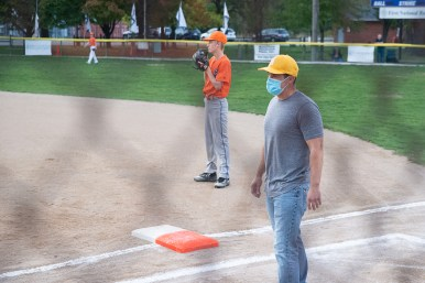 A LaGrange Park coach wears a mask while manning the first base line during the championship game of the Roy Overholt Tournament on Oct. 9. (Shanel Romain/Contributor)