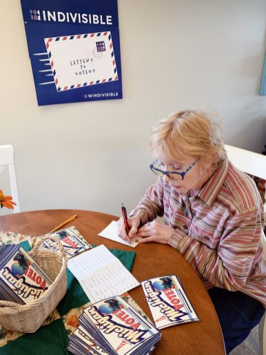 Brookfield resident Cathy Bartl writes a postcard to a Michigan voter as part of the Postcards to Swing States project. (PROVIDED)
