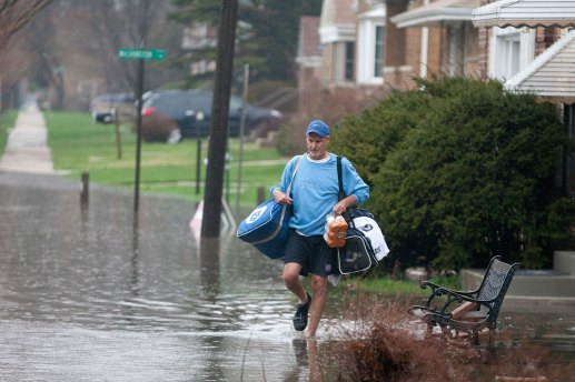 Thomas Stuart moves some of his belongings to his car on higher grounds as he escapes flooding on Prairie Avenue near Washington in Brookfield.
