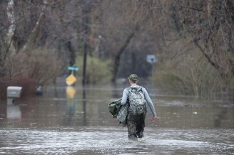 Tom Boyce makes his way down flooded Gladstone Avenue with groceries in his backpack. He has lived on the Riverside Lawn street for 34 years and said the block has endured five bad floods in that time.