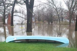 A canoe rests on the edge of flood waters on Gladstone Avenue in Riverside Lawn.