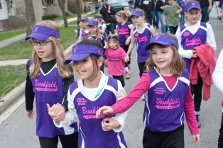 Allie Krueger, left, Emma Brass and Mary Hopkins march together down Grand Boulevard toward Kiwanis Park in the Brookfield Little League parade.