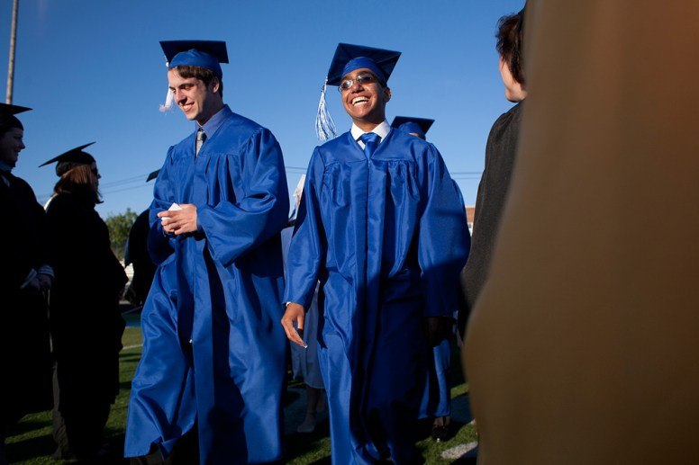 Graduate Daniel Gonzalez (right) walks onto the football field at RB High School to music and cheers on Friday.