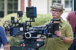 A crew member prepares a camera to shoot a scene.