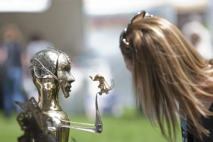A fest goer leans in for a closer look at a mixed media sculpture by artist James Eichorst at the Riverside Arts Weekend at Guthrie Park. (File 2013)