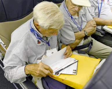 Bob Luebben sorts through the pile of letters he received during the flight back to Chicago. He received letters from neighbors, friends and from officials like Brookfield President Kit Ketchmark and RBHS Superintendent Kevin Skinkis. (Photo courtesy of Honor Flight Chicago)