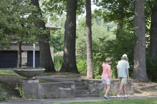 A couple walks past the front walkway of the Coonley Estate's bedroom wing, which has been vacant for the past four years. (Photo by David Pierini)