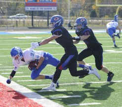 RBHS wide receiver Dean Zigulich is pushed out of bounds by a pair of Glenbard South defenders. (Photo by Jennifer Wolfe)