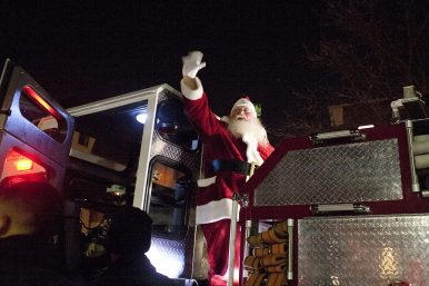 Santa arrives on the back of a firetruck to light the Christmas tree for the annual Riverside holiday stroll. (David Pierini/staff photographer)