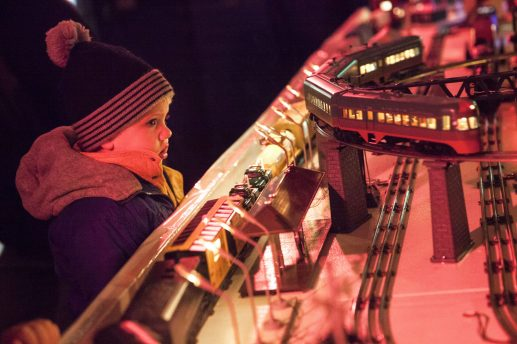 Hugh Holmes, age 2, stares mesmerized at the toy train display inside the Riverside Garage during the 40th Annual Holiday Stroll in downtown Riverside. (Photo by Rick Majewski)