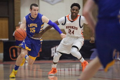 LTHS senior guard Harrison Niego, left, dribbles the ball up the court against OPRF guard Breshawn Wilkerson during the Lions' 60-51 win on Friday, December 20, 2014 (Chandler West/Staff Photographer)