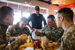 Jaime Flores (center), Owner of Tamale Hut Cafe, 8300 Cermak Road in North Riverside, serves some customers from the National Guard on Friday, February 6, 2015. | Chandler West/Staff Photographer