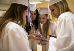 Graduating students of the Class of 2015 share their photos on their smartphones while waiting for the commencement ceremony at Riverside-Brookfield High School on May 22.   Ting Shen/Contributor