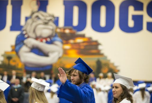 A graduating senior of class 2015 waves at family and friends. | Ting Shen/Contributor
