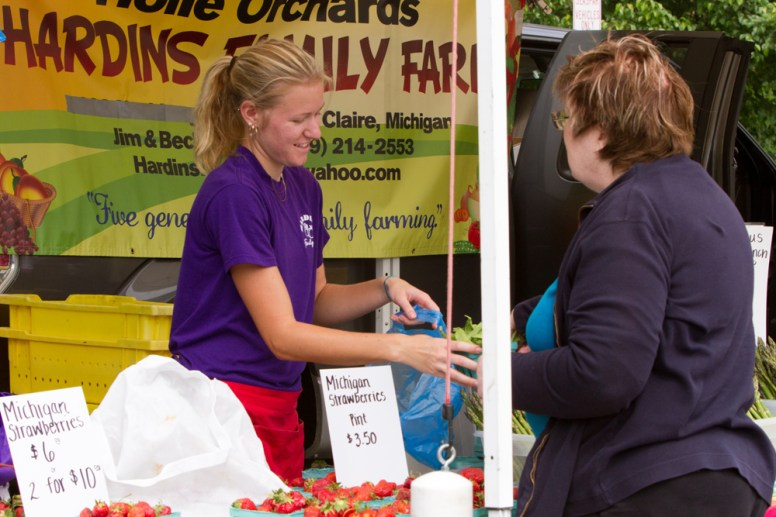 Ariana Zhem, left, of Hardins Family Farms, Eau Claire, Mich., bags produce for a customer at the Brookfield farmers market on Saturday, June 13, 2015. |Photo by Jennifer T. Lacey