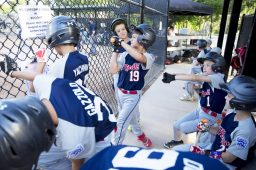 Riverside's Sam Thomas, center #19, practices his swing in the dugout while his teammates look on. (Contributing Photographer Ting Shen)