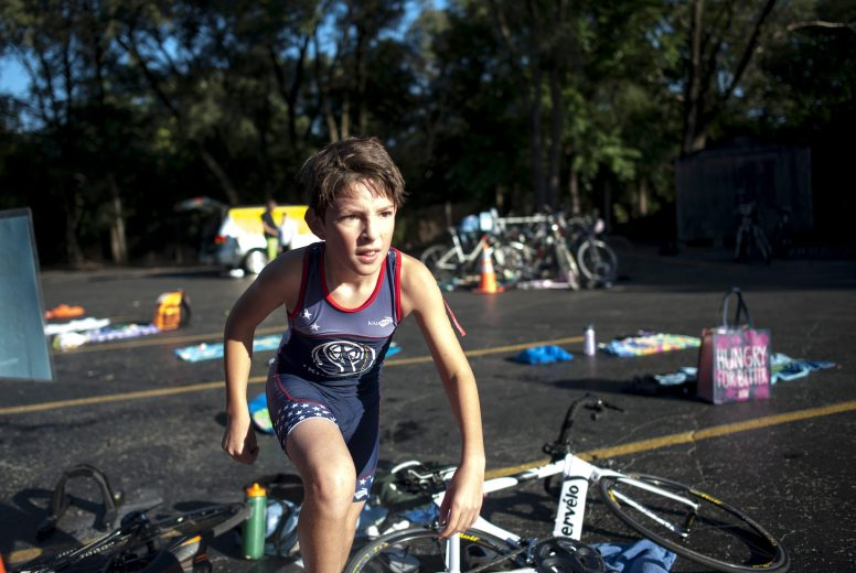 Alan Garza moves from the bike section to the running section during Cori's Kids Triathlon on Saturday morning Aug. 22, in Riverside. Participants swam, ran and biked around the village's First Division, and medals were given to first, second, and third place winners of the triathlon. | William Camargo/Staff Photographer