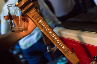 Hope Grutzius pours beer from Brickstone Brewing for guests at Hop Stop. | Stacey Rupolo/Contributor