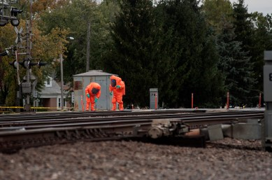 Firefighters in HAZMAT suits collect samples of a still-unknown substance that spilled onto the grade crossing at Maple Avenue in Brookfield on Oct. 12. The incident stopped train and vehicle traffic for hours. Staff Photographer/ William Camargo
