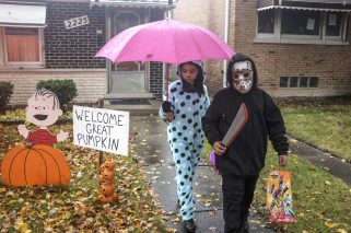 Jorge and Julia Camacho trick-or-treat in the 2200 block of Forest Avenue in North Riverside despite persistent rain on Halloween on Saturday, Oct. 31.   William Camargo/Staff Photographer