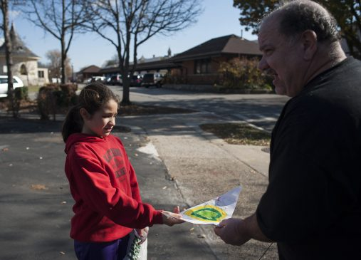 Main Covarrubias gives a note to a Riverside resident. | William Camargo/Staff Photographer