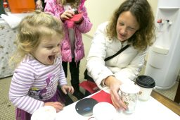 Margot Crist, 2, drinks hot chocolate with her mother, Jill Crist at Edward Jones. | Michelle Kanaar/Contributor