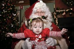 Santa Claus holds baby girl Samantha Jensen as she reaches out to her parents at The Irish Times Meet and Greet in Brookfield. | Arturo Hidalgo/Contributor