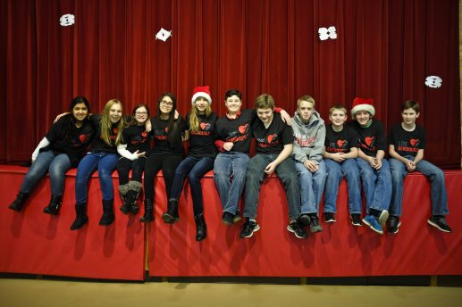 "Young volunteers to help the needy this Christmas in Brookfield, sit and wait on top of a stage at St. Paul's Lutheran Church wearing t-shirts saying ""Live Generously."" 