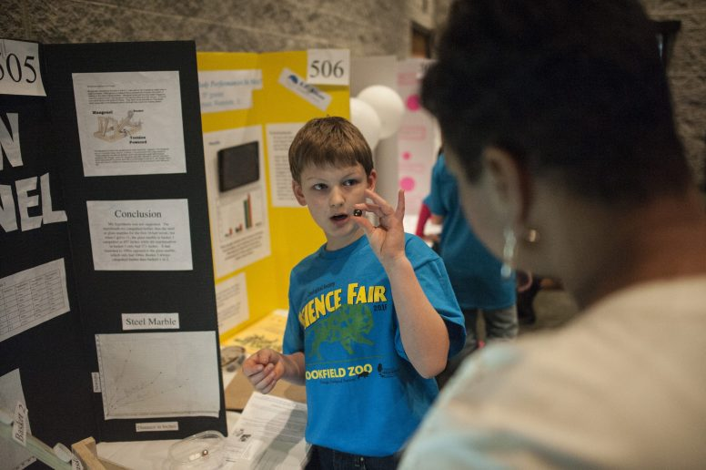 5th grader Aidan Makeeff from Ames Elementary shows a judge his science project during the Brookfield Zoo Science fair on Feb. 25. | William Camargo/Staff photography