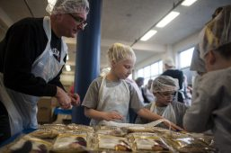 Deacon Dave helps Aubre Walsack and Tommy Soschski pack food. William Camargo/Staff Photographer
