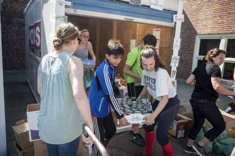 Hauser Junior High School students carry boxes of donated food, for a food drive that took place on April 16. | William Camargo/Staff Photographer