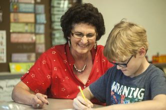 Jan Greenenwald helps Gabriel Anitra with some math work during class on May 26. Jan Greenenwald is retiring after 45 years of teaching. | William Camargo/Staff Photographer