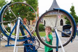 Ari Davis, 4, spins a bicycle wheel with beads on the spokes at the first Cruise Night in downtown Riverside. | Stacey Rupolo/Contributor