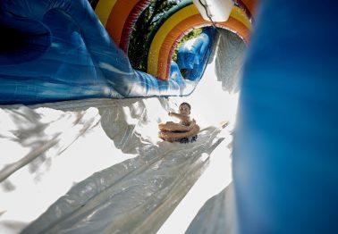 Prescott Bare zips down a water slide set up outside the Riverside Swim Club on July 14. | William Camargo/Staff Photographer