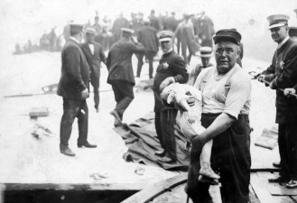 A man stricken with grief carries the body of a child away from the ship. | Courtesy of Eastland Disaster Historical Society