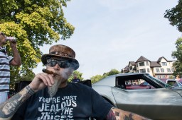 Dwayne Wisniewski puffs on stogie as people file by a 1970s Corvette. | Sebastian Hidalgo/Contributor