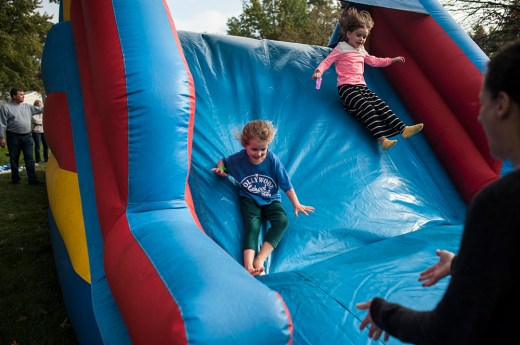 Annabeth Svebakken and Penelope Black slide down the inflatable slide during Fall Fest in Hollywood Elementary school in Brookfield on Oct. 15.   William Camargo/Staff Photographer