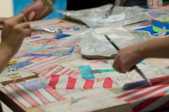 """Students at Hauser Junior High School created a multimedia art project incorporating """"thank you"""" messages to veterans and patriotic images underneath a painting of a stylized American flag. 