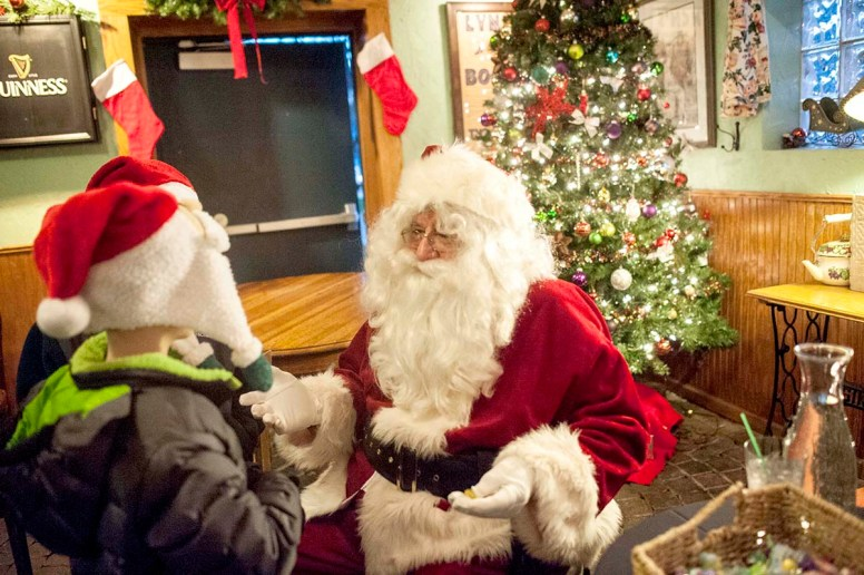 Santa Claus greets a child at Irish Times in downtown Brookfield prior to being whisked by fire truck to Eight Corners for the tree-lighting at 6 p.m. | William Camargo/Staff Photographer