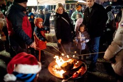 Families gather round the fire pit to roast marshmallows outside the Riverside Garage on East Avenue. | William Camargo/Staff Photographer