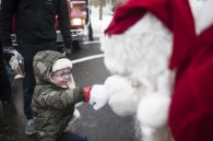 Santa fist bumps with Jack Flynn during one of his stops in North Riverside on Dec.17. | William Camargo/Staff Photographer