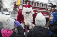 Santa Claus chats with kids during one of his stops in North Riverside on Dec. 17. Santa made nearly a dozen stops aboard a North Riverside fire truck during his annual tour to meet the village's children. | William Camargo/Staff Photographer