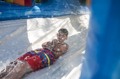 Eddie Melidis slides down a water slide set up outside the Riverside Swim Club on July 14. | William Camargo/Staff Photographer