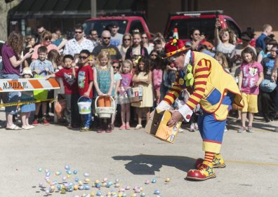 A clown helps spreadi the Easter eggs during annual Easter Egg Hunt on April 15 in North Riverside. | William Camargo/Staff Photographer