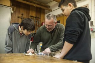 Komarek School teacher Dan Kartje goes over some details before letting students continue working to finish their wood working projects during a class in March.   William Camargo/Staff Photographer