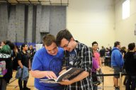 """RBHS seniors Ian Baartman and Derek Johnson share a laugh over the 2017 Rouser, distributed to students on May 19. The Rouser staff celebrated the 100th anniversary of the yearbook's first edition, given to the Class of 1918, by incorporating the theme of """"legacy"""" into this year's Rouser. 
