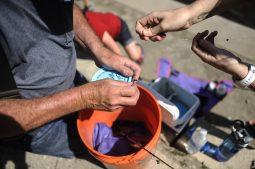 Parents help their children put some baits on their children fishing rods during the fishing derby on June 11. | William Camargo/Staff Photographer