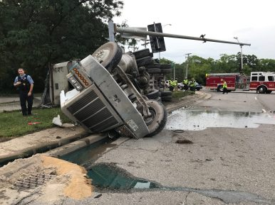 A truck hauling gravel flipped on its side after leaving the roadway south of 31st Street on First Avenue and continuing north across the roadway. The truck took out two light poles before coming to rest on the grass east of First Avenue. (Photo courtesy of the Riverside Fire Department)